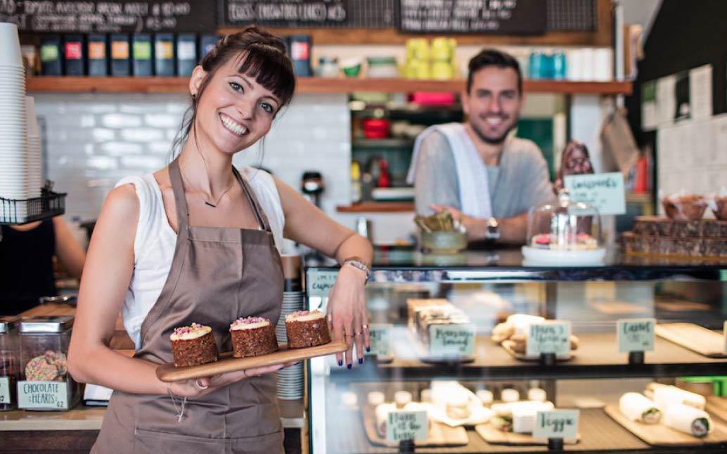 Micro empresaria  en su panadería, sonriendo a cámara como una de nuestras mujeres emprendedoras.