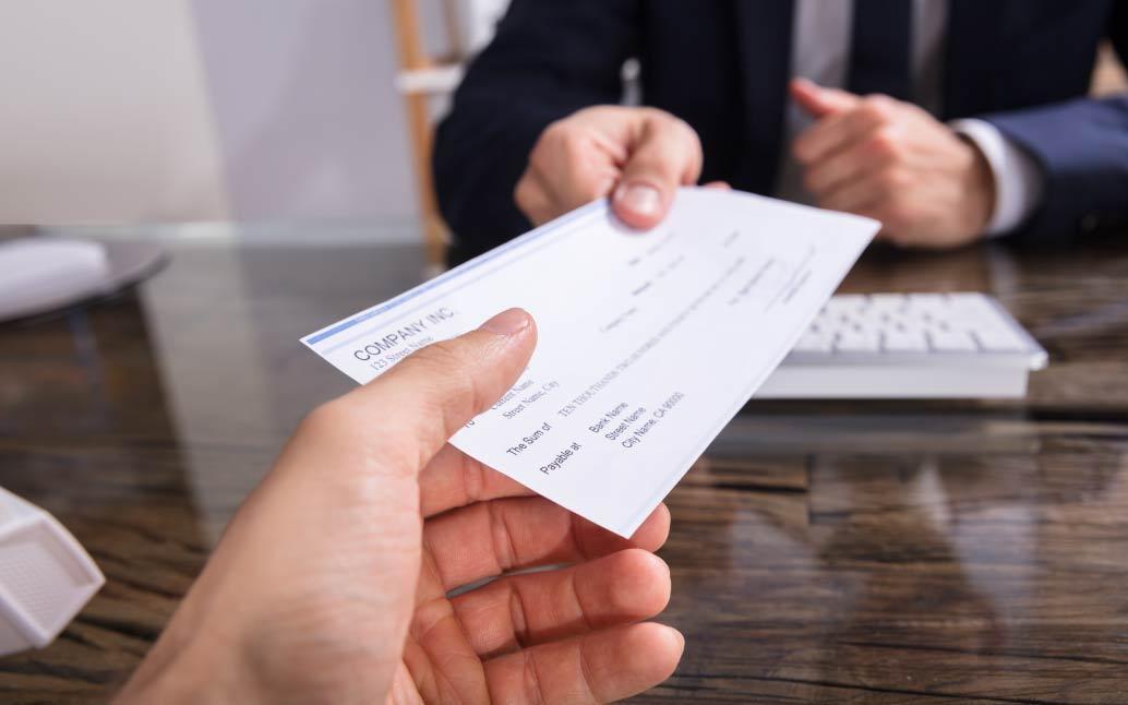 Imagen de manos de hombre que entrega cheque a otro hombre con los intereses de las cesantías